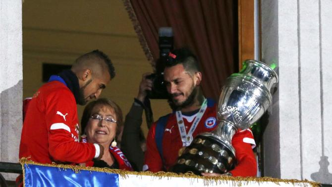 Chile's Arturo Vidal, Chile's president Michelle Bachelet and Chile's Marcelo Diaz stand on a balcony at the La Moneda presidential palace