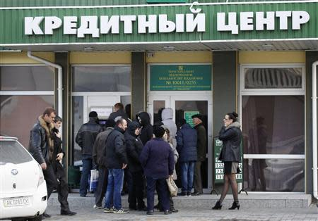 People queue to withdraw money outside a bank in Simferopol