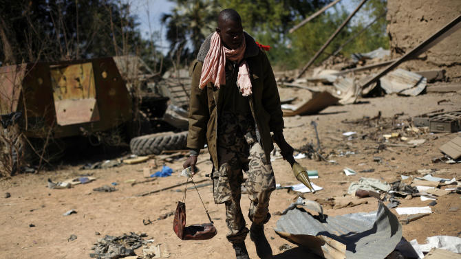 A Malian soldier walks inside a military camp used by radical Islamists and bombarded by French warplanes,  in  Diabaly, Mali,  some  460kms (320 miles) North of the capital Bamako Monday Jan. 21, 2013.  French and Malian troops took control Monday of the town of Diabaly, patrolling the streets in armored personnel carriers and inspecting the charred remains of a pickup truck with a mounted machine gun left behind by the fleeing militants. (AP Photo/Jerome Delay)