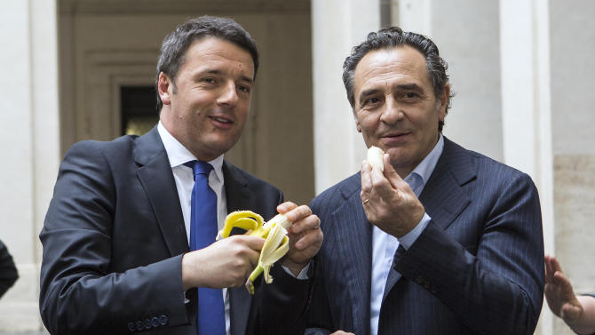 Italian premier Matteo Renzi, left, and Italian national soccer team coach Cesare Prandelli share a banana in solidarity to Barcelona Brazilian player Dani Alves, during a ceremony in Rome, Monday, April 28, 2014. Alves, who is black, was about to take a corner in Sunday's 3-2 win at Villarreal's El Madrigal Stadium when a banana landed on the pitch in front of him. The Brazil international picked it up, peeled it and ate some of it before throwing the rest aside. After the match, Alves said humor was the best way to combat racism in sport. That sentiment has led fellow football players, officials and even political figures from around the globe to respond with solidarity by picturing themselves eating a banana. (AP Photo/Roberto Monaldo, Lapresse) ITALY OUT