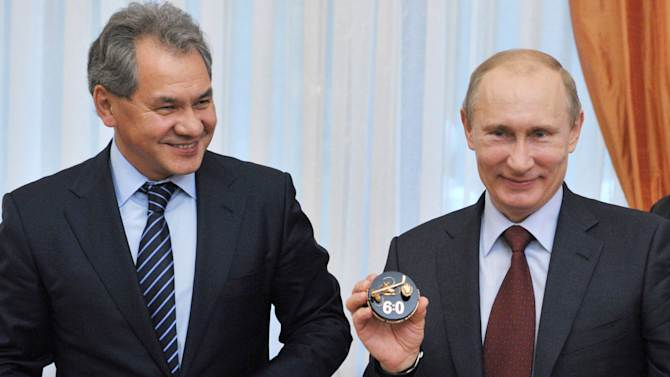 FILE - In this Thursday, Oct. 18, 2012 file photo, Russian President Vladimir Putin, right, flanked by Moscow region Governor Sergei Shoigu, meets with leaders of the Night Hockey League, in the Novo-Ogaryovo residence outside Moscow. Russian President Vladimir Putin has fired the country's defense minister two weeks after a criminal probe was opened into alleged fraud in the sell-off of military assets. Putin made the announcement of Anatoly Serdyukov's dismissal on Tuesday Nov. 6, 2012 in a meeting with Moscow regional governor Sergei Shoigu, whom he appointed as the new minister. (AP Photo/RIA-Novosti, Alexei Nikolsky, Presidential Press Service, file)
