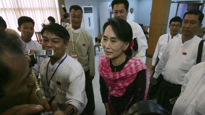 Myanmar Opposition Leader Aung San Suu Kyi, center, talks to journalists as she attends Central Executive Committee (CEC) meeting of her National League for Democracy party at a restaurant in Yangon, Myanmar, Monday, May 27, 2013. Suu Kyi, rights groups and Islamic leaders expressed dismay over plans by authorities in western Myanmar to revive a two-child limit on Muslim Rohingya families. (AP Photo/Khin Maung Win)