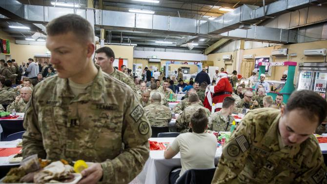 U.S. soldier from the 3rd Cavalry Regiment dressed as Santa Claus greets fellow soldiers eating a Christmas day lunch at forward operating base Gamberi in the Laghman province of Afghanistan