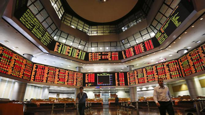 People walk in front of the trading board at a private stock market gallery in Kuala Lumpur, Malaysia, Monday, July 6, 2015. Asian markets mostly fell Monday as investors reacted to Greece's sound rejection of terms set by its international creditors, deepening uncertainties over its status as a member of the 19-nation eurozone. But Chinese shares rebounded after heavy losses last week. (AP Photo/Vincent Thian)