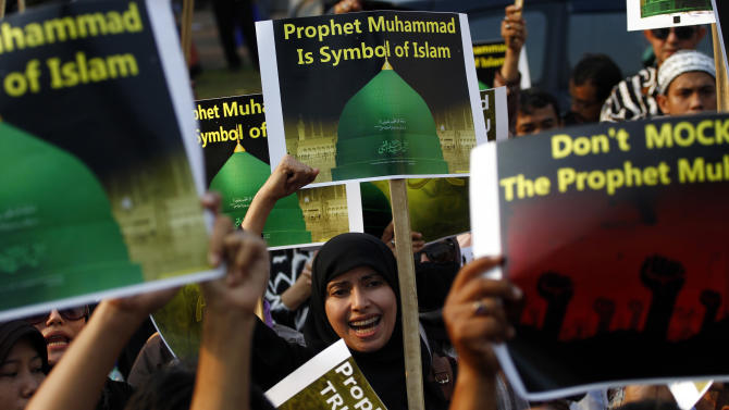"Indonesian Muslims shout slogans as they hold a banner which reads ""Prophet Muhammad is symbol of Islam"" during a protest against an anti-Islam film that has sparked anger among followers, outside the U.S. Embassy in Jakarta, Indonesia, Friday, Sept. 14, 2012.  The low-budget film ""Innocence of Muslims"" ridicules Islam and depicts the Prophet Muhammad as a fraud, a womanizer and a madman. Since it emerged on the Internet, it has prompted violent protests at U.S. embassies in the Middle East. In Libya, the American ambassador and three other staff members were killed when the U.S. consulate in Benghazi was attacked.  (AP Photo/Achmad Ibrahim)"