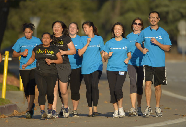 In this Tuesday, Dec. 11, 2012 photo, Zendi Solano, second from left, trains with her running club in Pasadena, Calif. Kaiser Permanente, one of the nation's largest nonprofit health insurance plans,