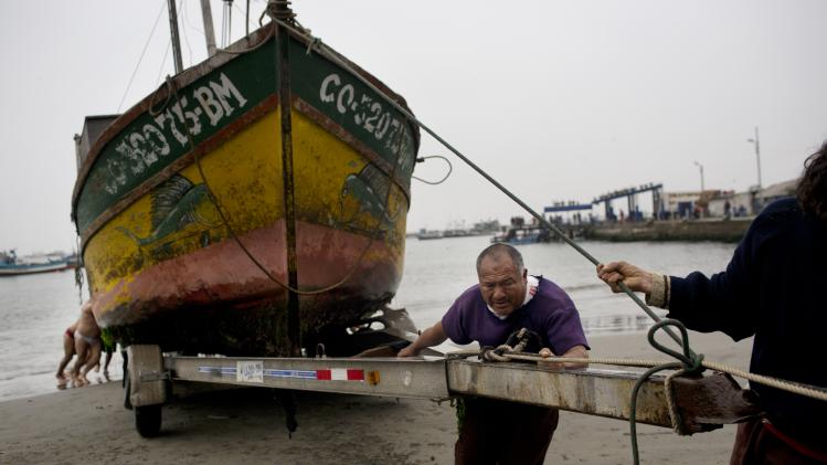 "Harbor workers push a boat to be repaired on to a trailer at the Ancon Harbor on the outskirts of Lima, Peru, Thursday, Aug. 21, 2014. Ancon is an old town that was known as the ""Fishermen's Town of Lancon"" during the Spanish Colonial period, and continues to be an active cove for local fishermen after the town became popular with beach goers. (AP Photo/Rodrigo Abd)"