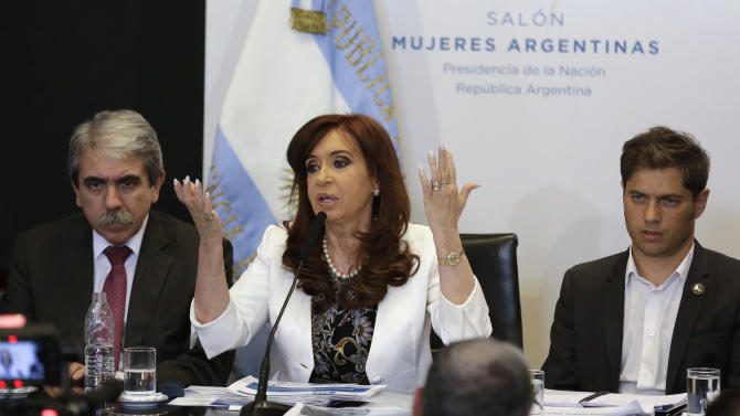 President Cristina Fernandez speaks, flanked by her Cabinet Chief Anibal Fernandez, left, and Economy Minister Axel Kicillof during the presentation of a new 100-peso bill at the Casa Rosada presidential palace in Buenos Aires, Argentina, Thursday, March 26, 2015.  A federal appeals court on Thursday threw out a case that accused Fernandez and other top officials of a major cover up deal with Iran, giving a victory of sorts to an administration that has been rocked by the mysterious death of the prosecutor who made the allegations. (AP Photo/Victor R. Caivano)