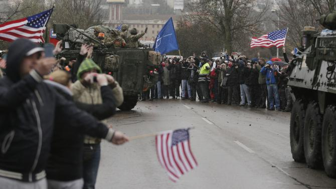 "US army soldiers wave to their supporters as they arrive with their convoy in Prague, Czech Republic, Monday, March 30, 2015. The ""Dragoon Ride"" convoy started last week from Estonia and passed through Latvia, Lithuania and Poland before entering the Czech Republic on a return journey to a German base. (AP Photo/Petr David Josek)"