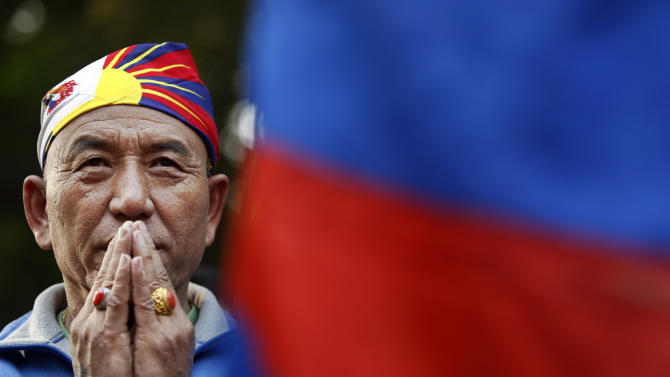 An exiled Tibetan Buddhist man prays during a rally to mark World Human Rights Day in New Delhi, Monday, Dec. 10, 2012. At least 86 people have set themselves on fire since 2009. (AP Photo/Tsering Topgyal)