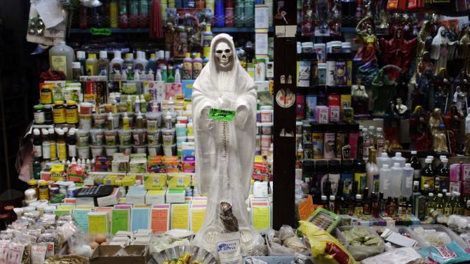 """FILE - In this April 9, 2009 file photo, a skeletal figure representing the folk saint known in Mexico as """"Santa Muerte"""" or """"Death Saint,"""" sits in a vendor's stall at a market in Ciudad Juarez, Mexico. Eight people have been arrested for allegedly killing two boys and a woman in ritual sacrifices by the cult of La Santa Muerte, or Saint Death, according to prosecutors in northern Mexico on Friday March 30, 2012. Jose Larrinaga, spokesman for Sonora state prosecutors, said the first of the three victims was apparently killed in 2009, the second in 2010 and the latest in March 2012. (AP Photo/Rodrigo Abd, File)"""