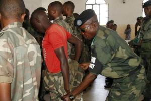 A Congolese soldier is stripped of his rank and uniform after the mass trial of 39 soldiers inside a military court in Goma in eastern DRC