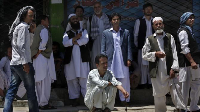 Afghan businessmen watch as others protest in front of Afghan Money Market,  condemning a June 23 armed robbery in downtown Kabul, near the U.S. embassy, in which, robbers stole $3.5 million from a truck, killing one man and injuring three other security guards in a area secured by Afghan police, in Kabul, Afghanistan, Saturday, June 25, 2011. (AP Photo/Gemunu Amarasinghe)