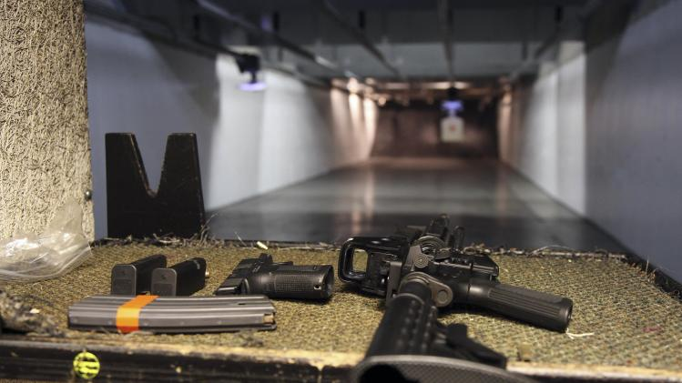 In this Jan. 4, 2013, photo, a rifle and a hand gun are displayed on the range of Sandy Springs Gun Club and Range, in Sandy Springs, Ga. In Connecticut and Colorado, scenes of the most deadly U.S. mass shootings in 2012, people were less enthusiastic about buying new guns at the end of the year than in most other states, according to an Associated Press analysis of new FBI data. The biggest surges in background checks for people who want to carry or buy guns occurred in states in the South and West. (AP Photo/Robert Ray)