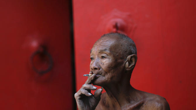 An elderly man smokes a cigarette during the Chinese New Year celebrations in Chinatown in Bangkok