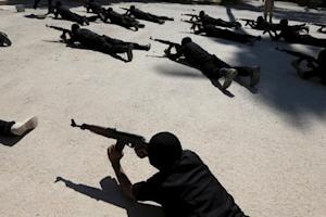 Rebel fighters aim their weapons as they demonstrate their skills during a military display as part of a graduation ceremony at a camp in eastern al-Ghouta, near Damascus, Syria