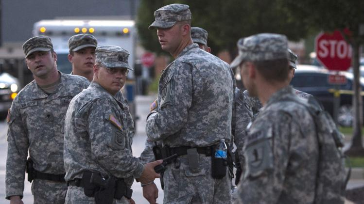 National Guard troops stand at a staging area located at a shopping center parking lot in Ferguson, Missouri