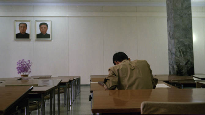 In this Sept. 10, 2012 photo, North Korean men study in desks beneath portraits of the country's late leaders, Kim Il Sung, left, and Kim Jong Il, at the Grand People's Study House in Pyongyang, North Korea. (AP Photo/David Guttenfelder)