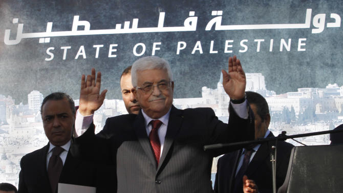 Palestinian President Mahmoud Abbas, waves to the crowd during celebrations for their successful bid to win U.N. statehood recognition in the West Bank city of Ramallah, Sunday, Dec. 2, 2012. Abbas returned home to a hero's welcome after winning a resounding endorsement for Palestinian independence at the United Nations. Israel on Sunday roundly rejected the United Nations' endorsement of an independent state of Palestine, announcing it would withhold more than $100 million collected for the Palestinian government to pay debts to Israeli companies.  (AP Photo/Nasser Shiyoukhi)