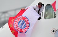 MUNICH, GERMANY - MAY 26:  A pilot flies a Bayern Muenchen flag from the cockpit window of the airplane returning the Bayern Muenchen team to Munich Aiport on May 26, 2013 in Munich, Germany.  (Photo by Lennart Preiss/Bongarts/Getty Images)
