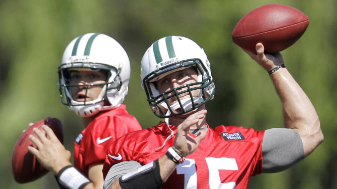 ADVANCE FOR WEEKEND EDITIONS, JULY 21-22 - FILE - In this May 31, 2012, file photo, New York Jets quarterbacks Mark Sanchez, left, and Tim Tebow workout during NFL football practice in Florham Park, N.J. The most popular guy on the Jets' roster isn't even a starter and has no defined role. Tebow is listed as a quarterback _ Sanchez's backup _ but Rex Ryan and the Jets envision as much more. (AP Photo/Julio Cortez, File)