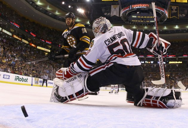 Blackhawks goalie Crawford looks back at the puck along with Bruins' Horton as a shot from Boychuk ties the game in the third period during Game 4 of their NHL Stanley Cup Finals hockey series in Bost