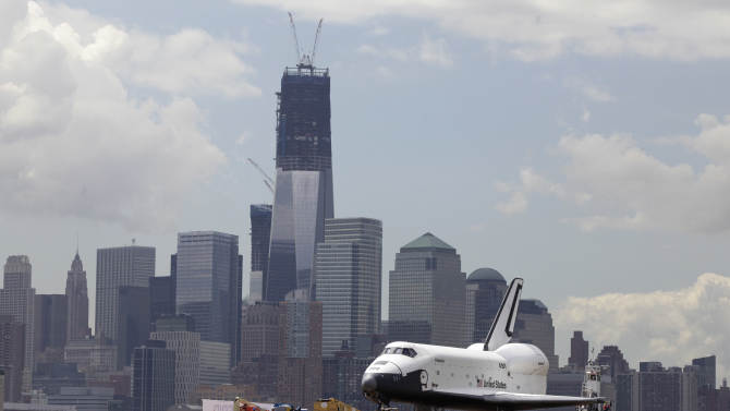 The space shuttle Enterprise passes lower Manhattan and One World Trade Center, under construction as it makes the final leg of its journey by barge to its new  home on the flight deck of the Intrepid Sea, Air & Space Museum. Wednesday, June 6, 2012. The U.S. space agency, NASA, ended its shuttle program last year. (AP Photo/Richard Drew)