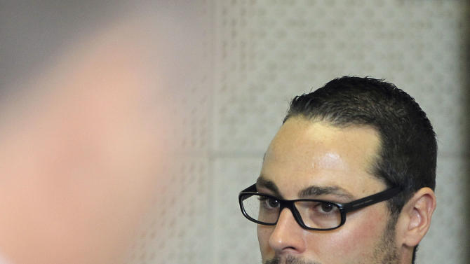 Carl Pistorius, brother of Oscar Pistorius, accused of murder, stands inside the court for his culpable homicide case at the Magistrate Court  in Vanderbijlpark, South Africa on Thursday April 25, 2013. (AP Photo/Themba Hadebe)