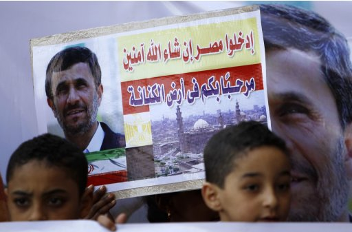 Children stand in front of a sign and a poster of Iran's President Mahmoud Ahmadinejad in front of the Al-Hussein mosque before Ahmadinejad's visit to the mosque in old Cairo