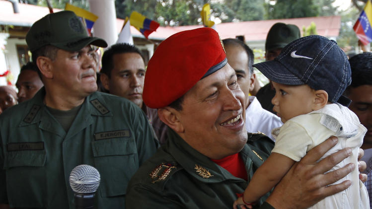 Venezuela's President Hugo Chavez carries a baby as he waits for the arrival of Ecuador's President Rafael Correa at the Fort Tiuna military base in Caracas, Venezuela, Tuesday, Dec. 14, 2010. Correa comes to Venezuela for a one-day visit. (AP Photo/Fernando Llano)