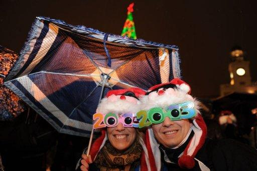 A couple wearing 2013 glasses celebrates at Puerta del Sol in Madrid on December 31, 2012