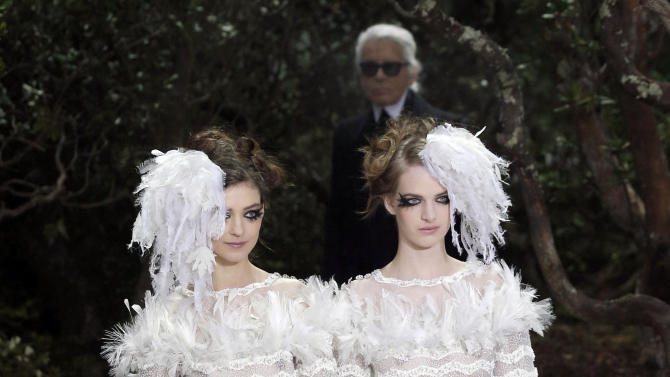 Models wear wedding gowns,  by German fashion designer Karl Lagerfeld for Chanel's Spring Summer 2013 Haute Couture fashion collection, presented in Paris, Tuesday, Jan. 22, 2013. Chanel's veteran couturier Karl Lagerfeld has used fashion to support a controversial French gay marriage law, sending two brides together down the catwalk.  He can be seen in the background. (AP Photo/Christophe Ena)
