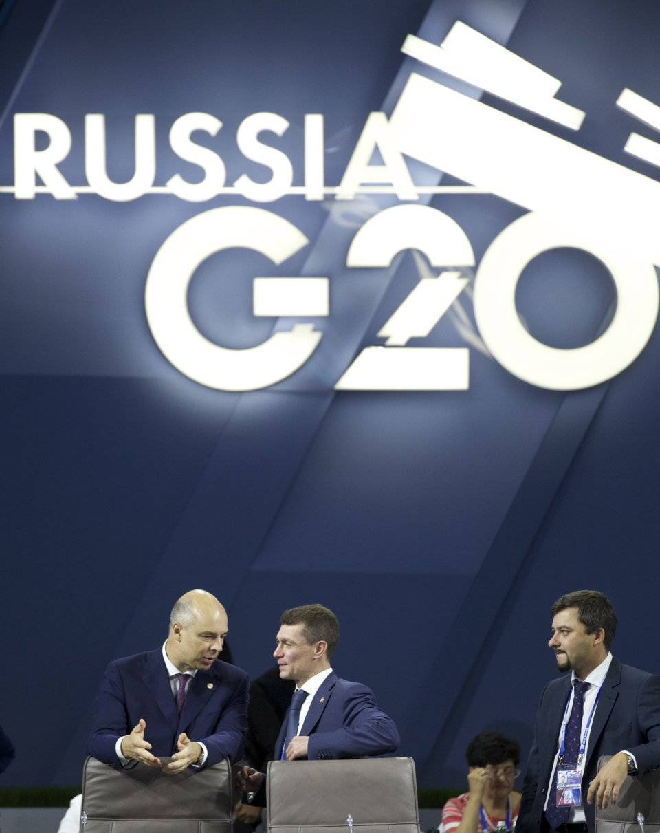 Russian Finance Minister Anton Siluanov, left, speaks to Russian Labor Minister Maxim Topilin at a meeting of the Group of 20 finance ministers in Moscow, Russia, Friday, July 19, 2013. Stashing profits offshore may soon get tougher for companies, thanks to an ambitious plan released Friday by the finance chiefs of leading world economies aimed at forcing multinationals to pay more taxes. (AP Photo/Alexander Zemlianichenko)