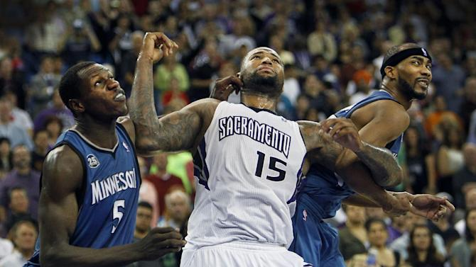 Sacramento Kings center DeMarcus Cousins (15) battles for a rebound against Minnesota Timberwolves Gorgui Dieng, left, and Dante Cunningham during the second half of an NBA basketball game in Sacramento, Calif., on Sunday, April 13, 2014.(AP Photo/Steve Yeater)
