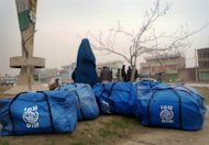In this Nov. 24, 2011 photo, an Afghan woman clad in a burqa stands near packed bags of humanitarian aid donated by International Organization for Migration (IOM) for drought-hit families in Mazar-e-Sharif, Balkh province, north of Kabul, Afghanistan. The United Nations appealed for $142 million on Oct. 1 to help those hit by the drought in 14 northern provinces where up to 80 percent of non-irrigated fields yielded little to no crops. So far, about $49 million has been pledged by aid groups, the U.S. and European nations. (AP Photo/Mustafa Najafizada)