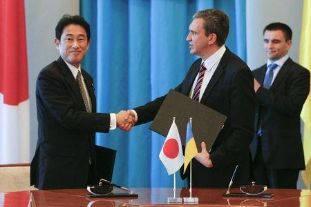 Minister of Economic Development and Trade of Ukraine Sheremeta shakes hands with Japan's Foreign Minister Kishida during a meeting in Kiev