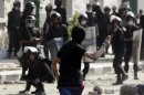 A protester throws a stone towards riot police, during clashes along a road which leads to the U.S. embassy, near Tahrir Square in Cairo