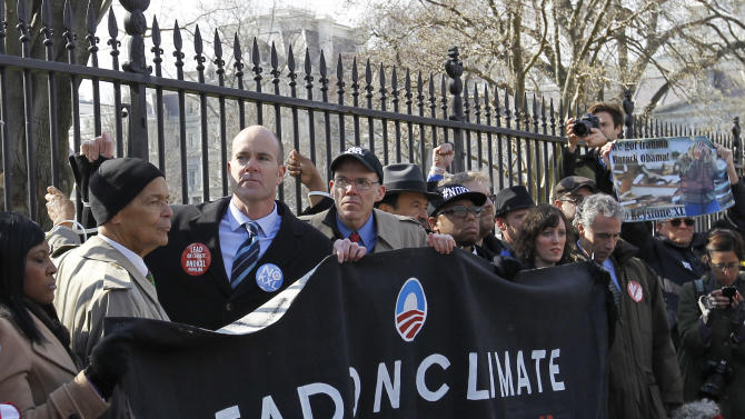 Civil rights protester Julian Bond, left, and Sierra Club Executive Director Michael Brune, second from left, gather with activists in front of the White House in Washington, Wednesday, Feb. 13, 2013, as prominent environmental leaders tied themselves to the White House gate to protest the Keystone XL oil pipeline. (AP Photo/Ann Heisenfelt)