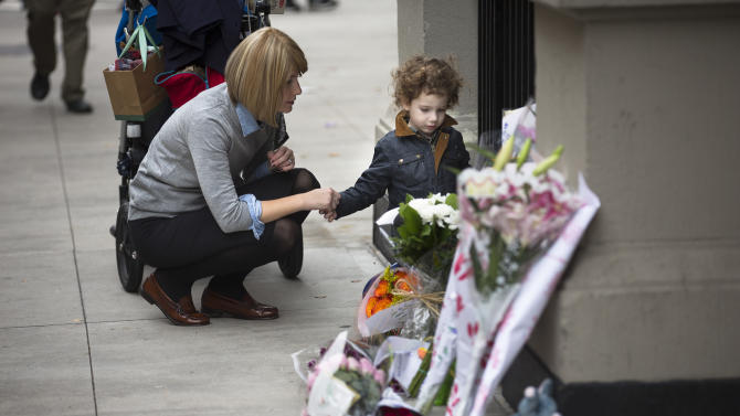 A woman holds a child's hand beside a memorial outside the apartment building where two children were allegedly stabbed by their nanny, Friday, Oct. 26, 2012, in New York. The 2-year-old son and 6-year-old daughter of a CNBC executive were found dead by their mother in a dry bathtub in the family's Upper West Side apartment Thursday night. The nanny suspected of stabbing the children was in critical condition Friday with apparently self-inflicted injuries.  (AP Photo/John Minchillo)
