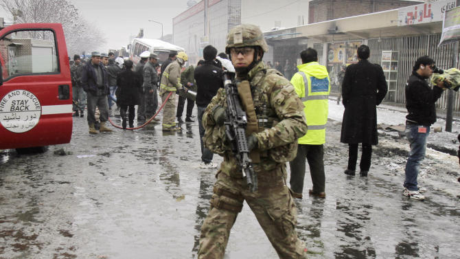 A U.S. soldier with the NATO- led forces walks at the scene of a suicide attack in Kabul, Afghanistan, Wednesday, Feb. 27, 2013. A man wearing a black overcoat and carrying an umbrella as a shelter against the heavy snow crossed a street in the Afghan capital early Wednesday morning toward an idling bus filled with Afghan soldiers, where he laid down and wiggled underneath. Then he exploded, engulfing the undercarriage of the bus in flames. (AP Photo/Ahmad Jamshid)