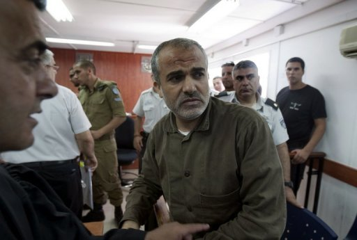 Palestinian Ibrahim Hamed looks over as he arrives in the docks where an Israeli military court will hand down a sentence at the Ofer military cour, near the West Bank city of Ramallah. An Israeli military court sentenced the former military leader of Hamas to multiple life sentences after convicting him of ordering the killing of dozens of Israelis