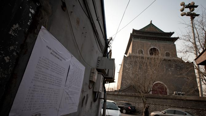 In this photo taken on Dec. 26, 2012, a woman walks past a Hutong house with a demolition notice placed on the wall, near the historical Drum and Bell Tower, right in the background, in Beijing.  The district government wants to demolish scuffed courtyard homes, move their occupants to bigger apartments farther from the city center and redevelop a square in 18th century Qing Dynasty fashion. (AP Photo/Andy Wong)