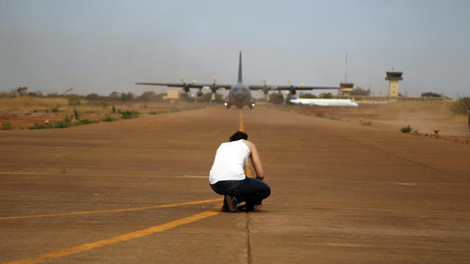 A camerawoman films the arrival of a French transport plane at Bamako's airport Tuesday Jan. 15 2013.  French forces led an all-night aerial bombing campaign Tuesday to wrest control of a small Malian town from armed Islamist extremists who seized the area, including its strategic military camp. A a convoy of 40 to 50 trucks carrying French troops crossed into Mali from Ivory Coast as France prepares for a possible land assault. Several thousand soldiers from the nations neighboring Mali are also expected to begin arriving in coming days. (AP Photo/Jerome Delay)