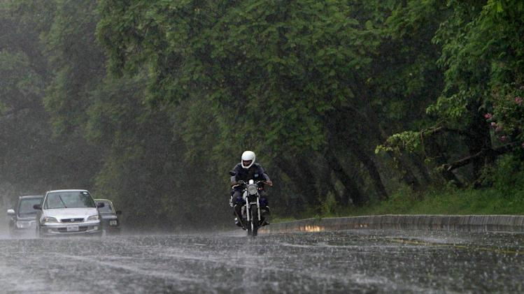 A Pakistani man drives his motorcycle as heavy rain pours on a highway in Islamabad, Pakistan, Tuesday, Aug. 6, 2013. (AP Photo/Anjum Naveed)