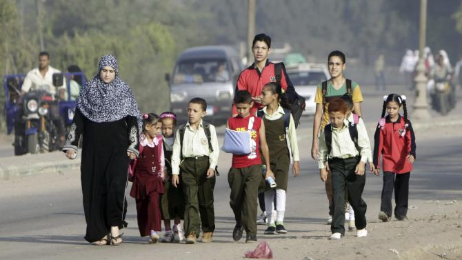 Students walk with their families to school on the first day of their new school year in Giza