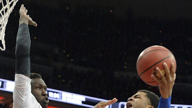 Kentucky's Andrew Harrison, right, shoots as Louisville's Mangok Mathiang defends during the first half of an NCAA college basketball game, Saturday Dec. 27, 2014, in Louisville, Ky. (AP Photo/Timothy D. Easley)