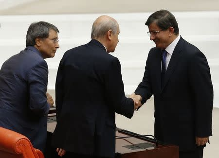 Newly-appointed acting Prime Minister and new AK Party leader Ahmet Davutoglu shakes hands with opposition leader Devlet Bahceli at the Parliament in Ankara
