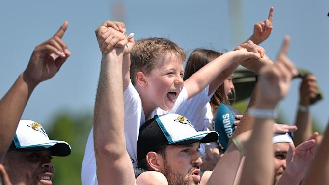 During the group photo Talan Craig, 7, got a great view from the shoulders of rookie center Luke Bowanko at an NFL football Jacksonville Jaguars' Got Skills Rookie Day on Friday, June 20, 2014, in Jacksonville, Fla