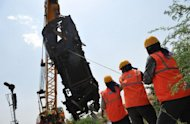 <p>A crane removes the mangled remains of a coach of the Bangalore-bound Hampi Express after it collided with a stationary goods train near Penneconda town in Ananthpur District, about 145 kms from Bangalore on Tuesday. Television footage from showed mangled, upturned coaches with rescue workers carrying out injured passengers on stretchers by torchlight</p>