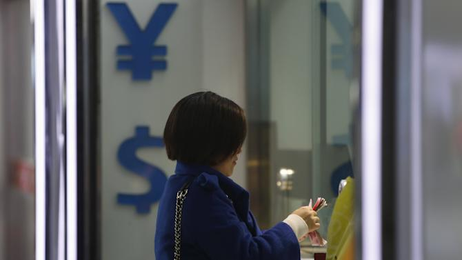 A woman counts Chinese yuan notes at a foreign exchange store in Shanghai